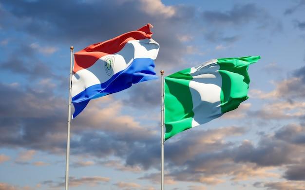 Beaux drapeaux des états nationaux du paraguay et du nigéria ensemble sur ciel bleu