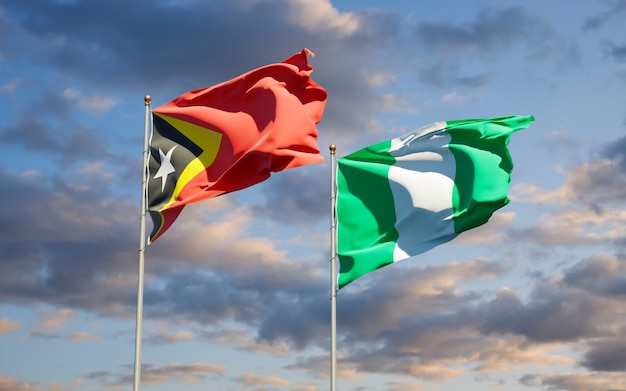 Beaux drapeaux des états nationaux du timor oriental et du nigéria ensemble sur ciel bleu
