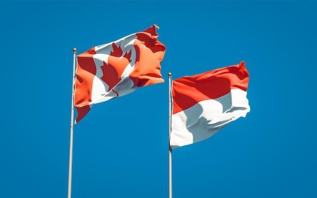Beaux drapeaux des états nationaux de l'indonésie et du canada ensemble sur ciel bleu