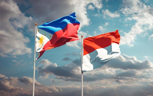 Beaux drapeaux des états nationaux des philippines et de l'indonésie ensemble sur ciel bleu