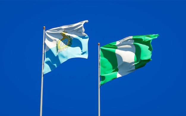 Beaux drapeaux des états nationaux de saint-marin et du nigéria ensemble sur ciel bleu