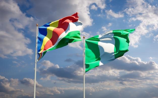 Beaux drapeaux des états nationaux des seychelles et du nigéria ensemble sur ciel bleu