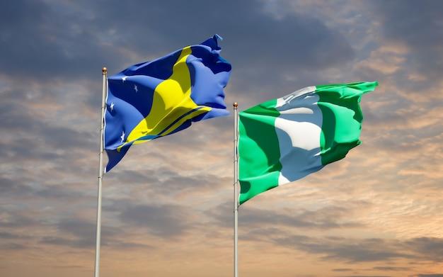 Beaux drapeaux des états nationaux de tokelau et du nigéria ensemble sur ciel bleu
