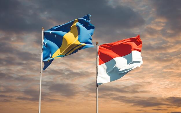 Beaux drapeaux des états nationaux de tokelau et de l'indonésie ensemble sur ciel bleu