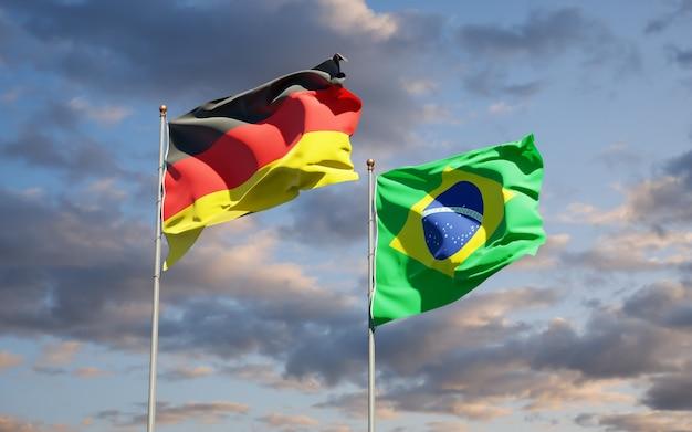 Beaux drapeaux nationaux de l'allemagne et du brésil ensemble sur ciel bleu