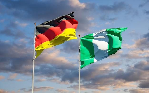 Beaux drapeaux nationaux de l'allemagne et du nigéria ensemble sur ciel bleu