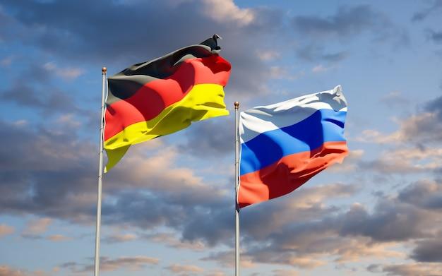 Beaux drapeaux nationaux de l'allemagne et de la russie ensemble sur le ciel bleu. illustration 3d