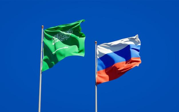 Beaux drapeaux nationaux de l'arabie saoudite et de la russie ensemble sur le ciel bleu. illustration 3d