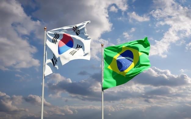 Beaux drapeaux nationaux de la corée du sud et du brésil ensemble sur ciel bleu