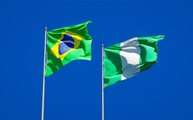 Beaux drapeaux nationaux du brésil et du nigéria ensemble sur ciel bleu
