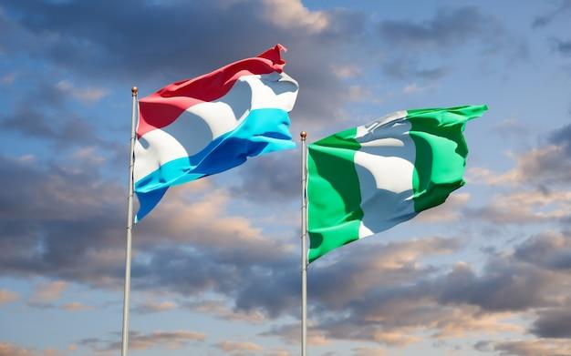 Beaux drapeaux nationaux du luxembourg et du nigéria ensemble sur ciel bleu