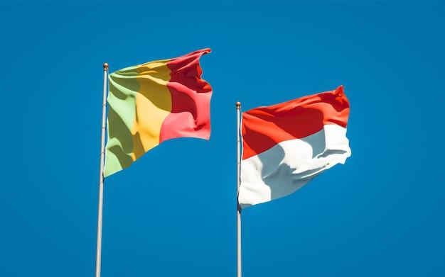 Beaux drapeaux nationaux du mali et de l'indonésie ensemble sur ciel bleu