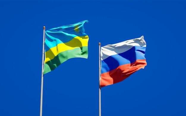 Beaux drapeaux nationaux du rwanda et de la russie ensemble sur le ciel bleu. illustration 3d