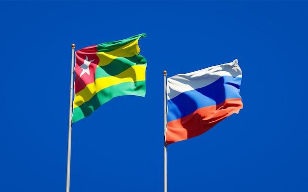Beaux drapeaux nationaux du togo et de la russie ensemble sur le ciel bleu. illustration 3d