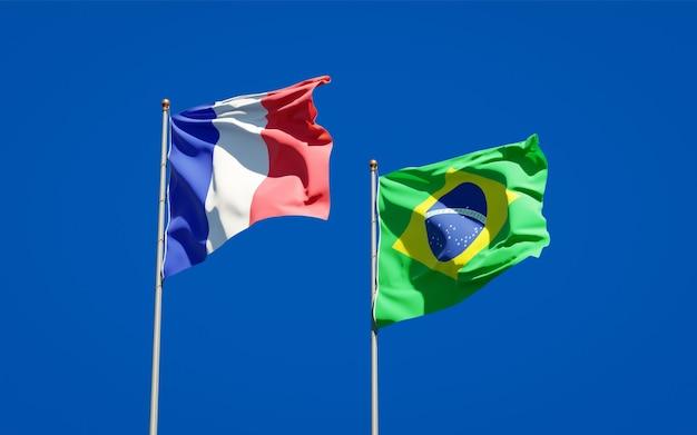 Beaux drapeaux nationaux de la france et du brésil ensemble sur ciel bleu