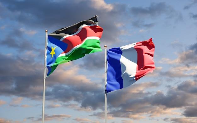 Beaux drapeaux nationaux de la france et du soudan du sud ensemble au ciel
