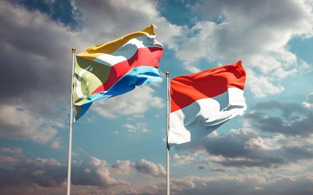 Beaux drapeaux nationaux de l'indonésie et des comores ensemble sur ciel bleu