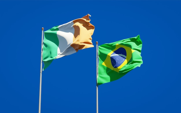 Beaux drapeaux nationaux de l'irlande et du brésil ensemble sur ciel bleu