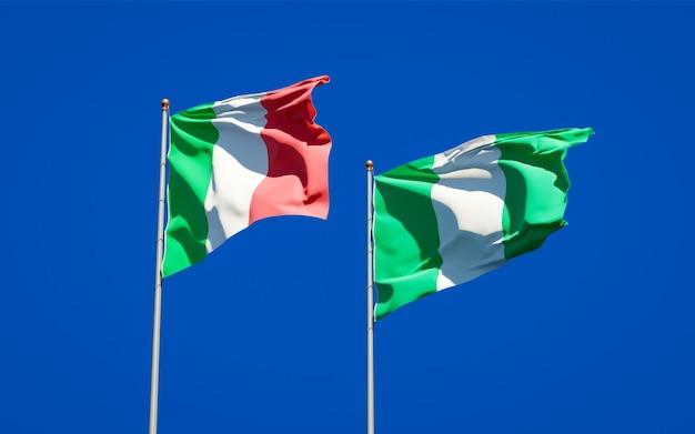 Beaux drapeaux nationaux de l'italie et du nigéria ensemble sur ciel bleu