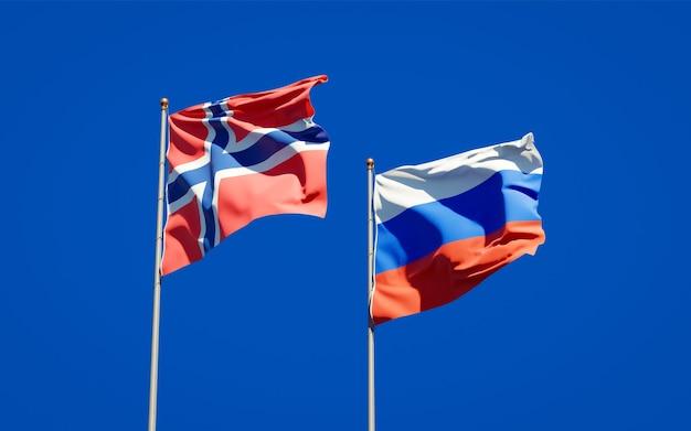 Beaux drapeaux nationaux de la norvège et de la russie ensemble sur le ciel bleu. illustration 3d