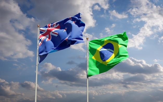 Beaux drapeaux nationaux de la nouvelle-zélande et du brésil ensemble sur ciel bleu
