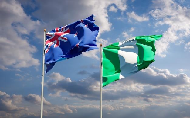 Beaux drapeaux nationaux de la nouvelle-zélande et du nigéria ensemble sur ciel bleu
