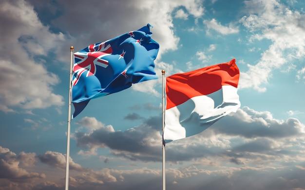 Beaux drapeaux nationaux de la nouvelle-zélande et de l'indonésie ensemble sur ciel bleu