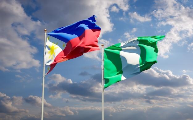 Beaux drapeaux nationaux des philippines et du nigéria ensemble sur ciel bleu