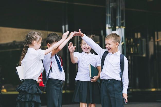 Beaux écoliers actifs et heureux sur le fond de l'école en uniforme