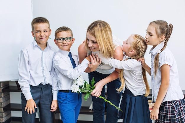 Beaux enfants écoliers avec des fleurs pour les enseignants à l'école en vacances