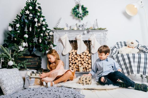 Beaux enfants jouant dans la chambre avec arbre cristmas et cheminée. concept de vacances d'hiver.