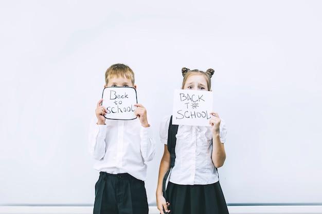 Beaux enfants sont des étudiants ensemble dans une classe à l'école sur fond blanc, les conseils reçoivent une éducation heureuse