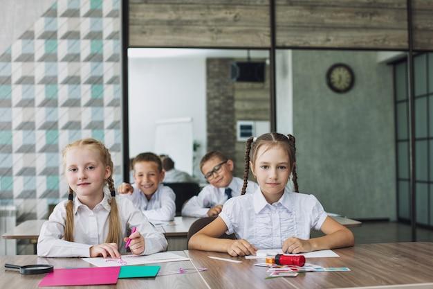 Les beaux enfants sont des étudiants ensemble dans une salle de classe à l'école reçoivent une éducation heureuse