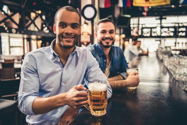 Les beaux gars boivent de la bière en regardant la caméra.