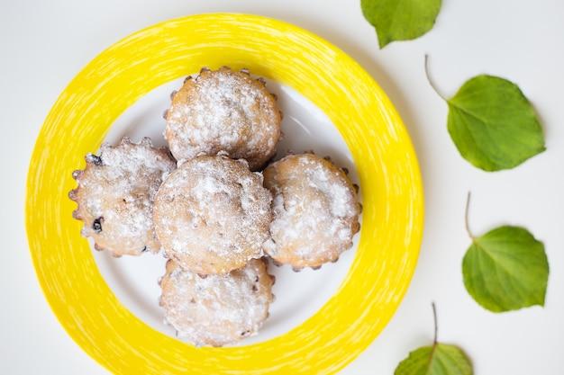Beaux gâteaux avec du sucre en poudre sur une assiette jaune.