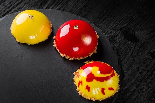 Beaux gâteaux recouverts de glaçage rouge et jaune brillant concept design desserts pâtissiers
