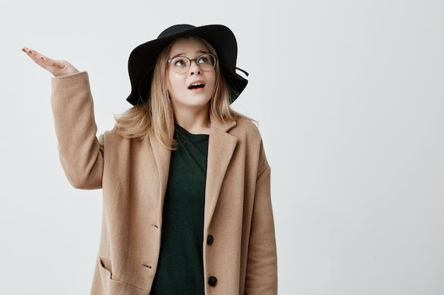De beaux gestes féminins confus avec perplexité, essaie de se rassembler avec des pensées, regarde vers le haut isolé. jeune, femme, mécontent, expression, porter, manteau, chapeau