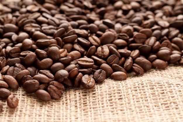 De beaux grains de café parfumés sont dispersés sur de la jute. photo de grains de café sous un léger angle