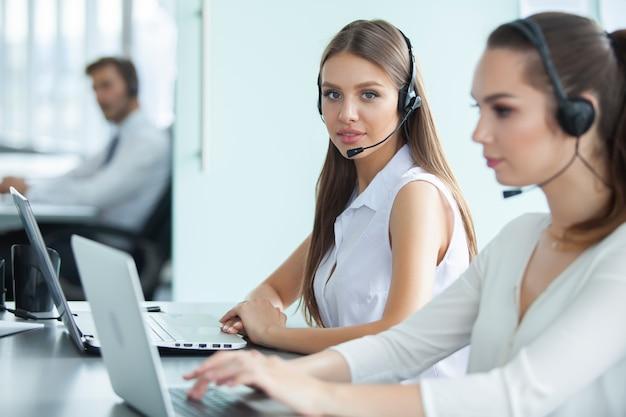 De beaux hommes d'affaires dans des casques utilisent des ordinateurs et sourient tout en travaillant au bureau. fille regarde la caméra.