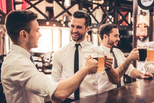 De beaux hommes d'affaires parlent et sourient.
