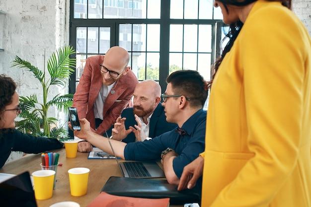 De beaux hommes d'affaires utilisent des gadgets, parlent et sourient pendant la conférence au bureau. mise au point sélective