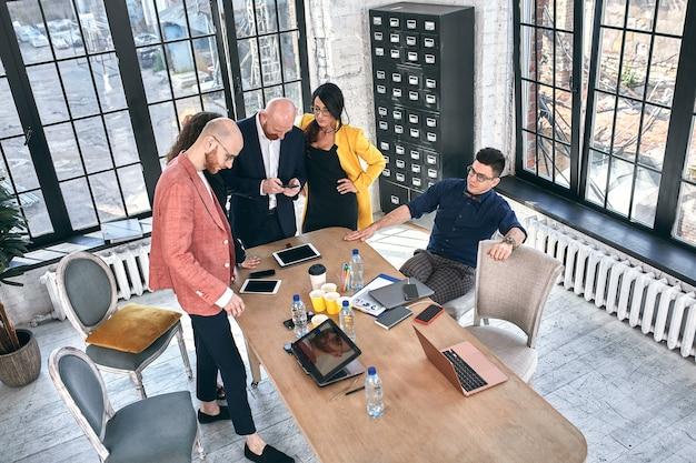 De beaux hommes d'affaires utilisent des gadgets, parlent et sourient pendant la conférence au bureau