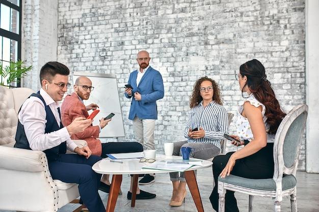 De beaux hommes d'affaires utilisent des gadgets, parlent et sourient pendant la conférence au bureau.