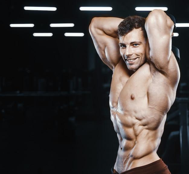 Beaux hommes athlétiques forts pompage des muscles musculation d'entraînement