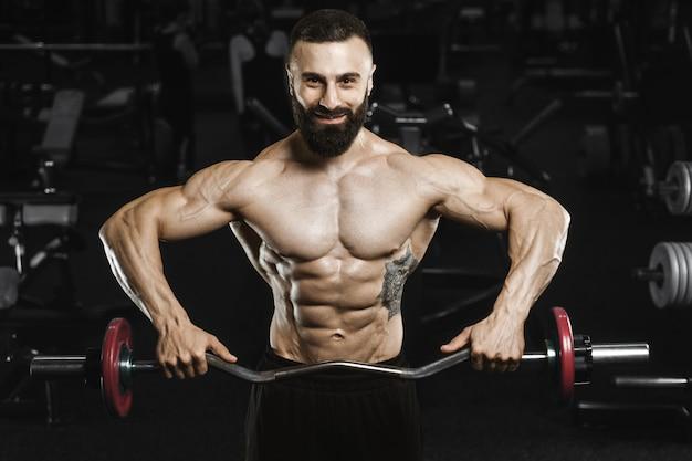 Beaux hommes athlétiques forts pompage des muscles séance d'entraînement haltères curl concept de musculation curl