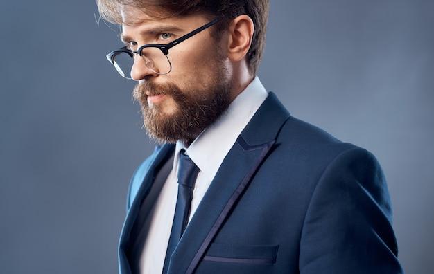 Beaux hommes en costume classique sur un modèle de fond sombre avec des lunettes vue recadrée.