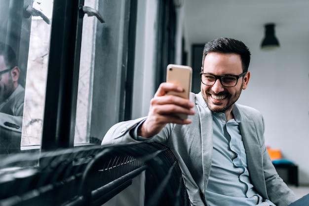 Beaux hommes souriants utilisant un téléphone assis près de la fenêtre. fermer.