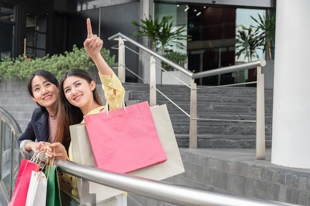 Beaux jeunes amis asiatiques avec sac à provisions et pointant quelque chose d'intéressant au grand magasin