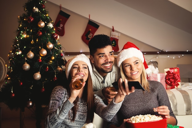 De beaux jeunes amis heureux regardent la télévision pour la veille de noël avec du pop-corn et des boissons.