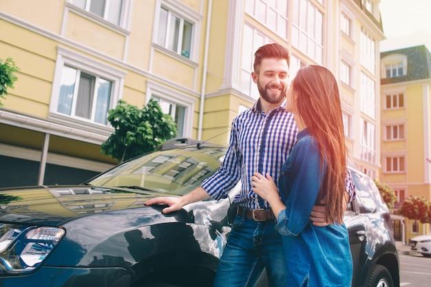 Beaux jeunes hommes debout près de la voiture chez le concessionnaire étreignant sa petite amie et tenant une clé